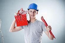 Junger Mann mit Bauhelm hält Werkzeug, Portrait