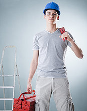 Junger Mann mit Bauhelm hält Werkzeug