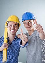 Zwei fröhliche junge Männer mit Bauhelmen, Portrait