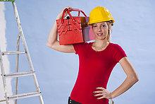Junge Frau mit Bauhelm trägt einen Werkzeugkasten