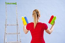 Junge Frau steht mit verschiedenen Fardosen vor einer Wand