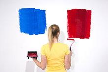 Junge Frau streicht eine Wand