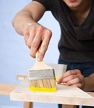 Junger Mann streicht ein Holzbrett