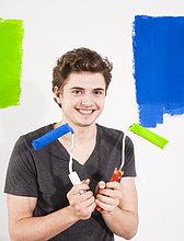 Lächelnde junger Mann streicht eine Wand