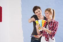Junges Paar betrachtet verschiedene Wandfarben