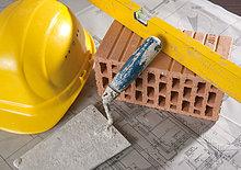Wasserwaage, Ziegelstein, Maurerkelle, Bauhelm und Bauplan