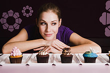 Portrait of young woman looking at row of cupcakes