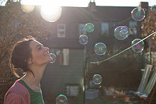 Junge Frau im Freien mit Blasen schweben in der Luft