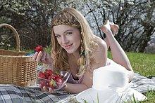 Blonde Frau liegt mit Erdbeeren auf einer Decke