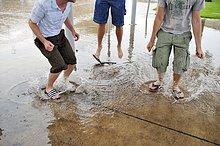 Drei junge Männer springen in Pfützen