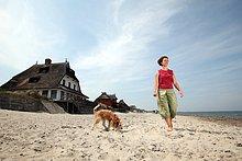 Frau mit Hund am Strand in Graswarder, Schleswig-Holstein, Deutschland