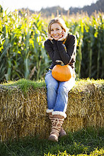 Mais,Zuckermais,Kukuruz,hinter,Frau,Kälte,sitzend,lächeln,Bauernhof,Hof,Höfe,auf dem Schoß sitzen,Feld,Herbst,Heu,Bündel,Nachmittag,Kürbis