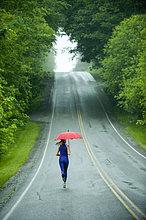 Europäer ,Frau ,Regenschirm, Schirm ,rennen ,Fernverkehrsstraße