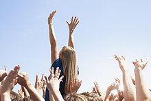 Frau mit erhobenen Armen über einer Menschenmenge