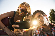 Drei Freunde gucken ein Video auf einem Handy