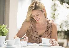 Frau ,schreiben ,Cafe ,Zeitschrift ,Außenaufnahme ,Tisch