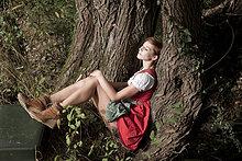 Frau im Dirndl sitzt an einem Baum