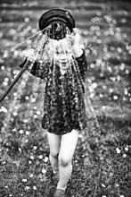 Kleiner Junge spielt mit dem Gartenwasserschlauch