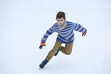Junge läuft Schlittschuh auf einem gefrorenen See