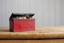 Antike Dose voller Geld auf Schreibtisch