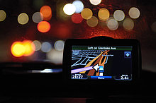 GPS Navigationsgerät an der Windschutzscheibe eines Autos bei Nacht