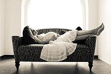 Schwangere Frau liegt auf dem Sofa