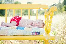 liegend, liegen, liegt, liegendes, liegender, liegende, daliegen ,Neugeborenes, neugeboren, Neugeborene ,gelb ,Sitzbank, Bank ,Feld ,Mädchen ,Baby
