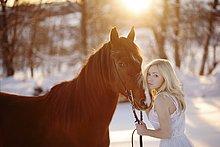 Junge Frau im weißen Kleid mit Pferd im Winter