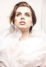 Junge Frau stützt Kopf auf Hand, Porträt vor weißem Hintergrund