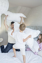 Father and children having pillow fight
