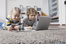 liegend,liegen,liegt,liegendes,liegender,liegende,daliegen,benutzen,Boden,Fußboden,Fußböden,Notebook,Bruder,Schwester,Tablet PC