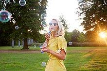 junge Frau,junge Frauen,Portrait,blasen,bläst,blasend,Sonnenuntergang,gelb,Blase,Kleidung,Kleid