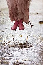 Kaukasischen Mädchen in Regen Stiefel springen in Regen Pfützen