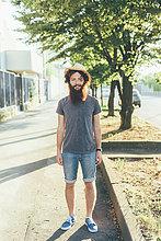 Portrait der jungen männlichen Hipster tragen Strohhut auf Bürgersteig