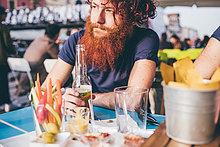 Junge männliche Hipster mit roten Haaren und Bart trinken Flaschen Bier an Bürgersteig Bar