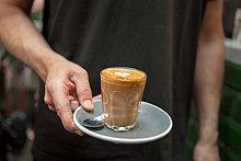 Gefrorener Schuss von Barista mit Glas Kaffee im Cafe