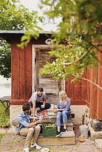 Freunde essen Wassermelone und trinken beim Sitzen außerhalb Hütte