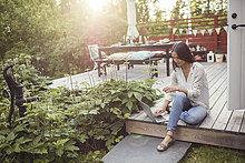 High Angle View der Frau mit Laptop beim Sitzen auf der Diele im Patio im Hinterhof
