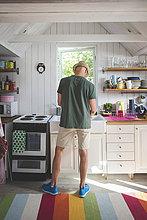Rückansicht des Mannes, der in der Küche zu Hause arbeitet