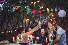 Glückliche Freunde, die Getränke trinken beim Genießen bei Gartenparty
