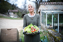 Portrait of mature female gardener with bowl of tomatoes and spring greens
