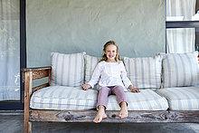 Portrait der lächelnden blonden kleinen Mädchen sitzen auf Couch oo der Terrasse