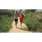 Mature couple jogging on path, rear point of view