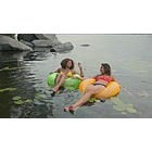 Young women floating on rubber rings in lake