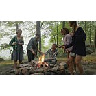 Friends toasting marshmallows over campfire in forest