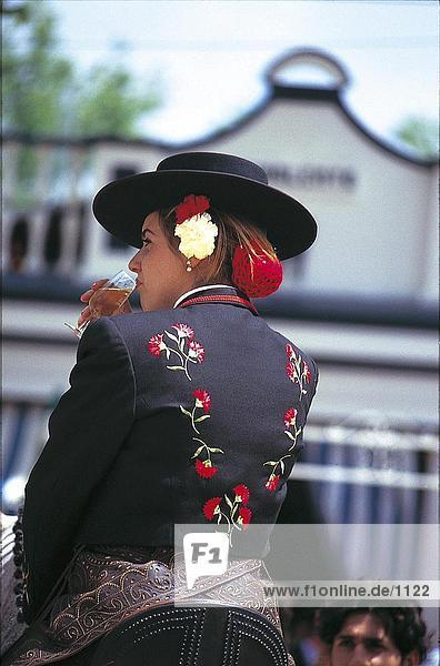Woman sitting on horse and drinking cherry drink at festival of andalusian horse  Jerez De La Frontera  Andalusia  Spain