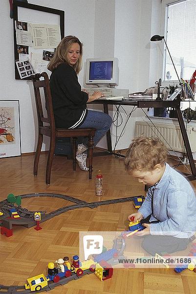 Frau blickt auf ihr Sohn spielen mit Spielzeug  Deutschland