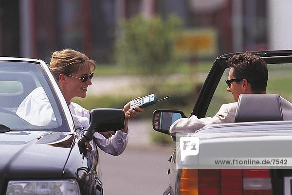 Frau hält ein schnurloses Telefon mit einem Mann in einem Auto sitzt