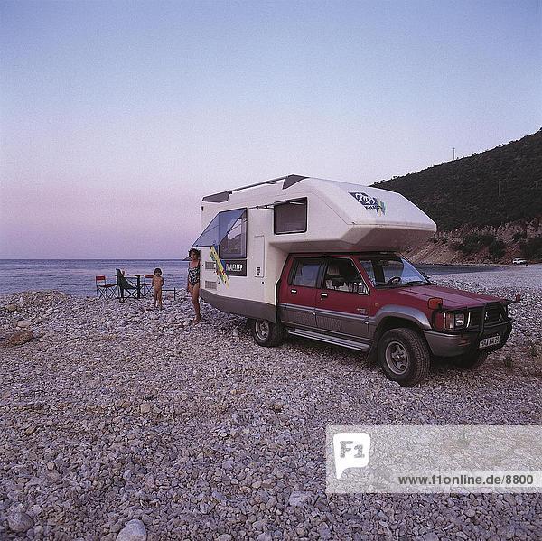 Frau stehend am Strand mit ihrem Sohn in der Nähe von Wohnwagen  Leonidion  Peleponnes  Griechenland