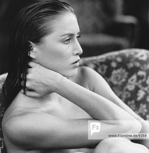 Porträt von eine nackte junge Frau Denken auf einer couch Porträt von eine nackte junge Frau Denken auf einer couch